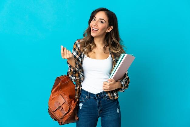 Donna giovane studente isolata sulla parete blu che fa gesto di soldi