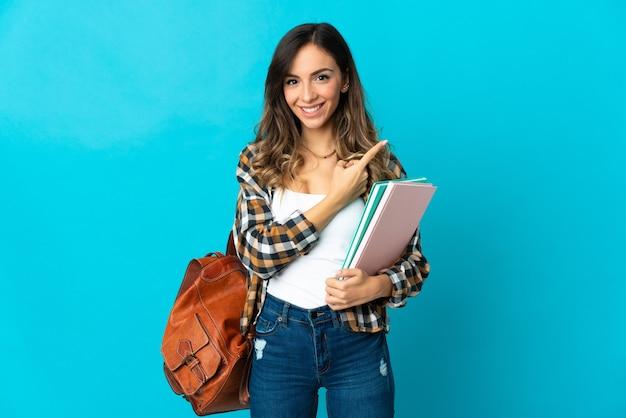 Donna giovane studente isolata sulla parete blu che punta di lato per presentare un prodotto