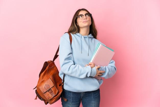 Donna giovane studente isolata sul rosa e alzando lo sguardo