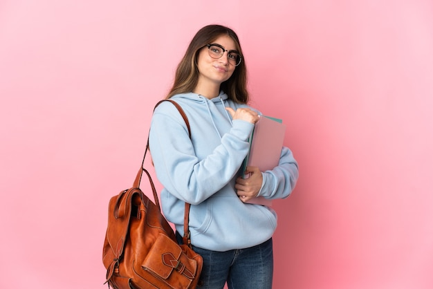 Donna giovane studente isolata sul rosa orgoglioso e soddisfatto di sé
