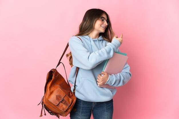 Donna giovane studente isolata sulla parete rosa che punta indietro