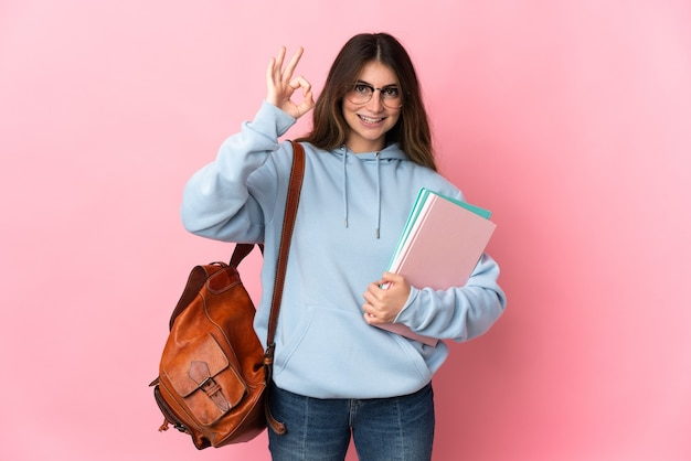 Donna giovane studente isolata sulla parete rosa che mostra segno giusto con le dita