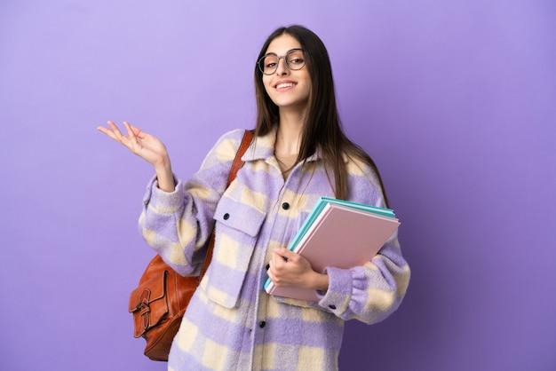 Giovane studentessa isolata su sfondo viola che allunga le mani di lato per invitare a venire