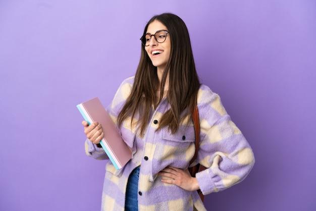Donna giovane studente isolata su sfondo viola in posa con le braccia all'anca e sorridente