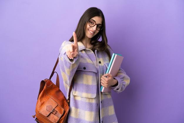 Giovane studentessa isolata su sfondo viola che mostra e alza un dito