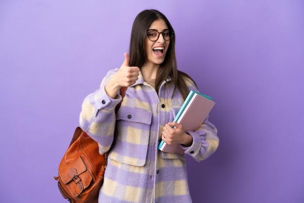 Giovane studentessa isolata su sfondo viola con il pollice in alto perché è successo qualcosa di buono