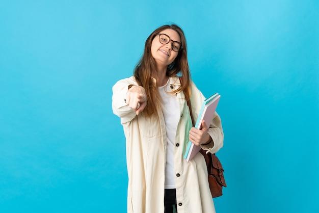 Giovane donna dell'allievo sopra la parete isolata che indica la parte anteriore con l'espressione felice