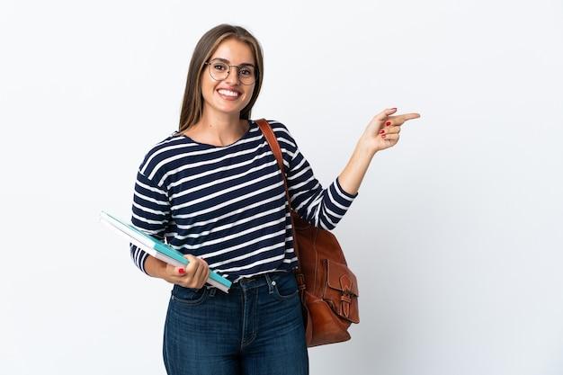 Donna giovane studente isolata su sfondo bianco che punta il dito a lato