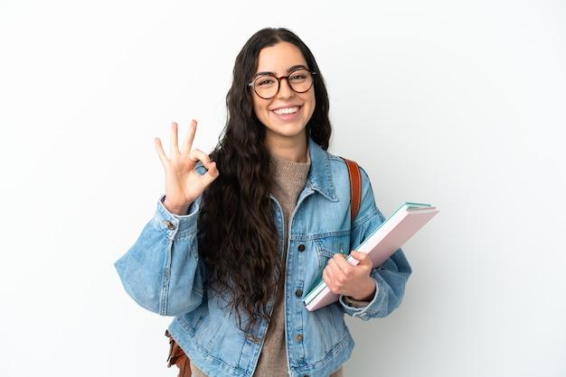Donna giovane studente isolata su sfondo bianco che mostra segno ok con le dita