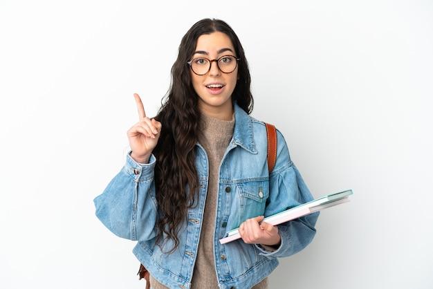Donna giovane studente isolata su sfondo bianco pensando un'idea puntando il dito verso l'alto
