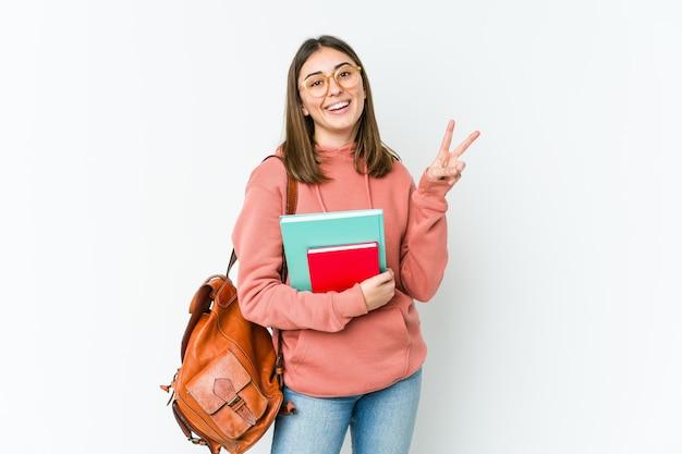 Giovane donna studentessa isolata sul muro bianco gioiosa e spensierata che mostra un simbolo di pace con le dita