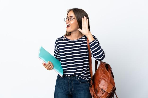 Donna giovane studente isolata sul muro bianco ascoltando qualcosa mettendo la mano sull'orecchio