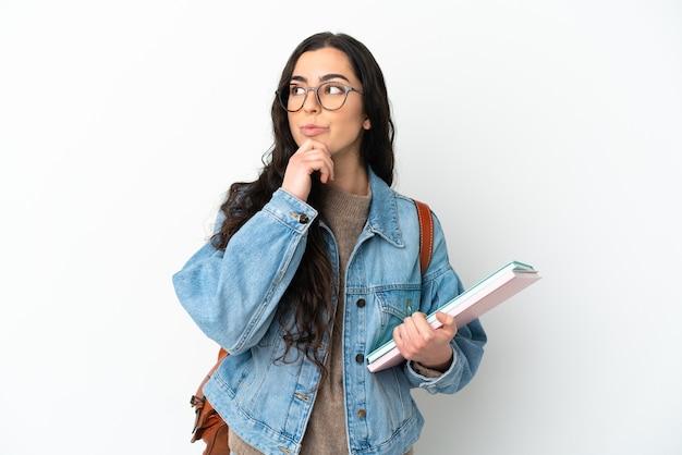 Donna giovane studente isolata sul muro bianco e alzando lo sguardo
