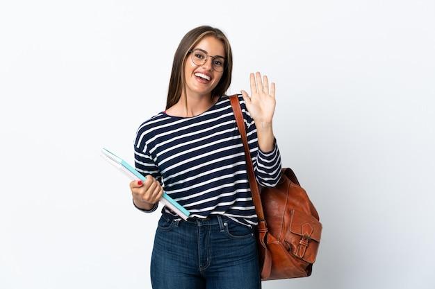 Donna giovane studente isolata sulla parete bianca che saluta con la mano con l'espressione felice