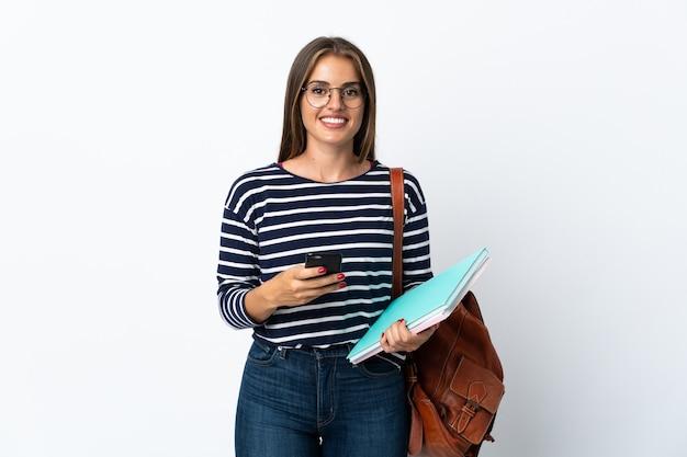 Donna giovane studente isolata sul muro bianco, inviando un messaggio con il cellulare