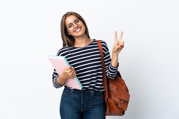 Donna giovane studente isolata sul muro bianco che mostra il segno di vittoria con entrambe le mani
