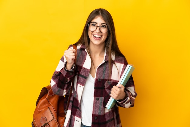 Donna giovane studente isolata su sfondo giallo che celebra una vittoria nella posizione del vincitore