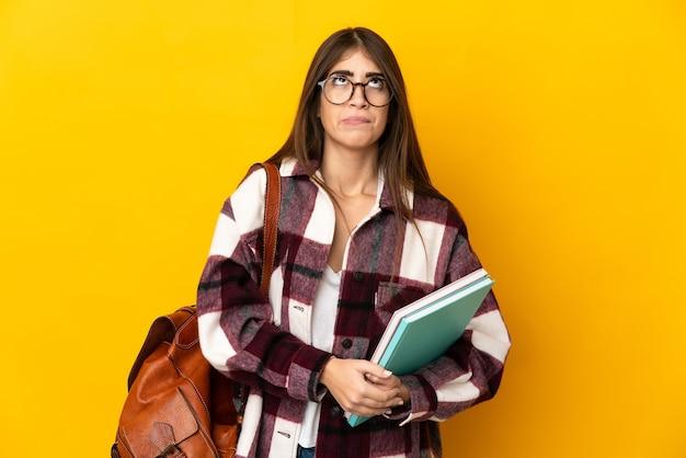 Donna giovane studente isolata su sfondo giallo e alzando lo sguardo