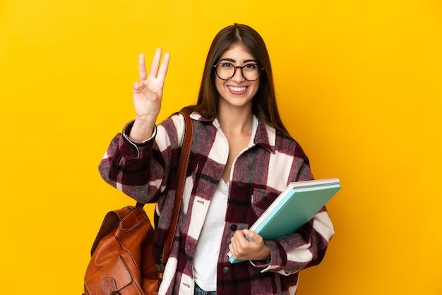Donna giovane studente isolata sulla parete gialla felice e contando tre con le dita