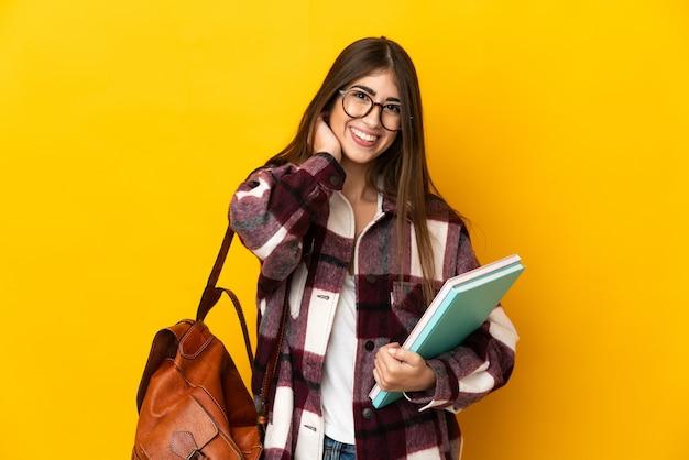 Donna giovane studente isolata sulla risata gialla della parete