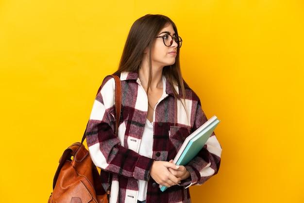 Donna giovane studente isolata sulla parete gialla che osserva al lato