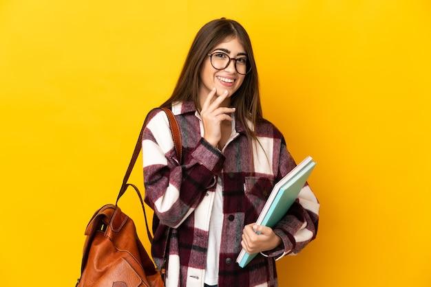 Donna giovane studente isolata sulla parete gialla che osserva in su mentre sorride