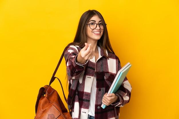Donna giovane studente isolata sulla parete gialla che fa gesto di soldi