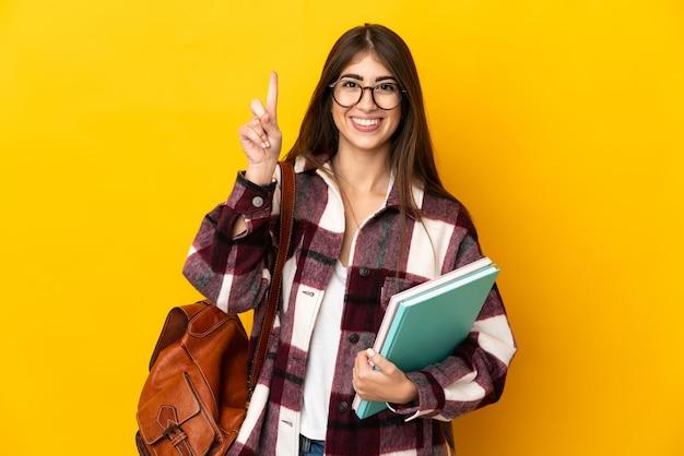 Donna giovane studente isolata sulla parete gialla rivolta verso l'alto una grande idea