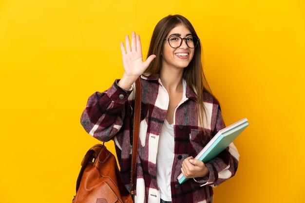 Giovane donna dell'allievo isolata sulla parete gialla che saluta con la mano con l'espressione felice