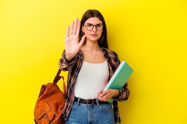Donna giovane studente isolata sul muro giallo in piedi con la mano tesa che mostra il segnale di stop, impedendoti.