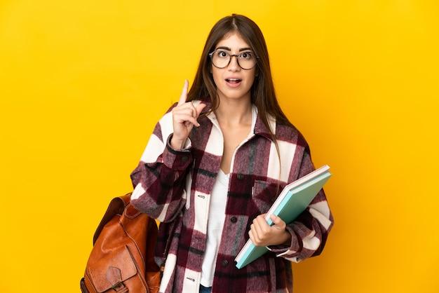 Giovane donna dell'allievo isolata sulla parete gialla che pensa un'idea che indica il dito verso l'alto