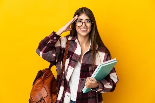 Donna giovane studente isolata sulla parete gialla con espressione di sorpresa