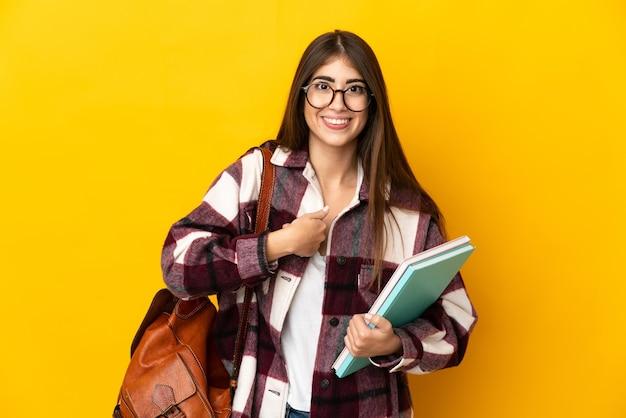 Donna giovane studente isolata sulla parete gialla con l'espressione facciale di sorpresa