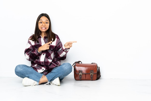 Giovane donna dello studente che si siede sul pavimento spaventato e che indica il lato