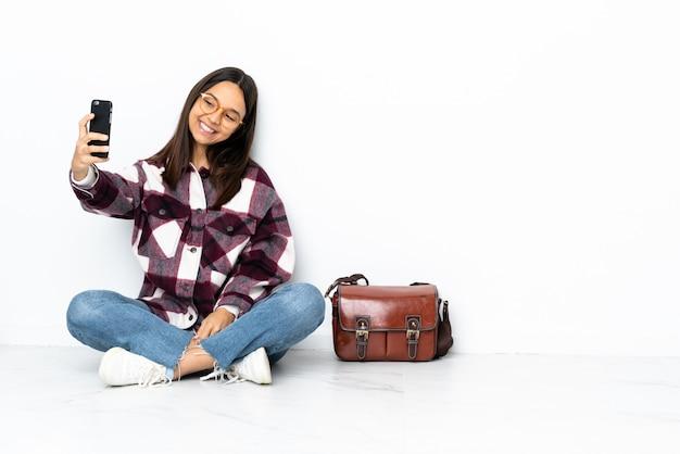 Giovane donna dello studente che si siede sul pavimento che fa un selfie