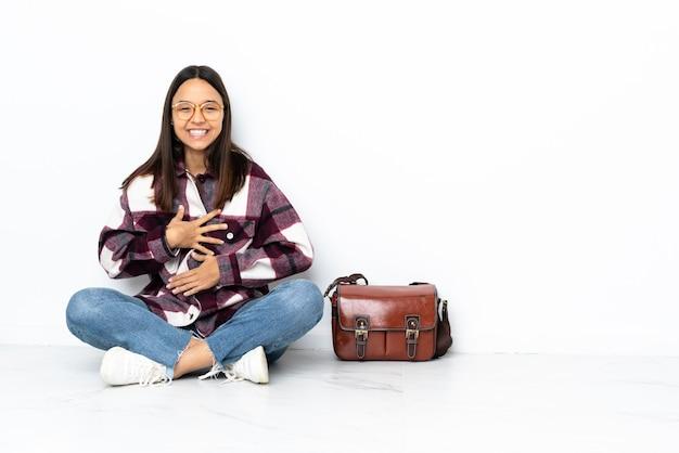 Giovane donna dell'allievo che si siede sul pavimento che sorride molto