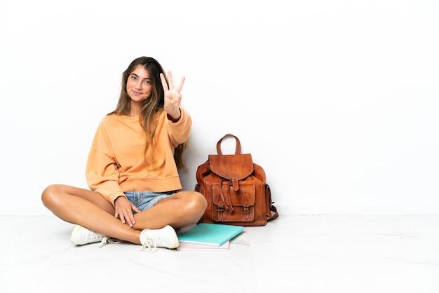 Donna giovane studente seduto sul pavimento con un laptop isolato su sfondo bianco felice e contando tre con le dita