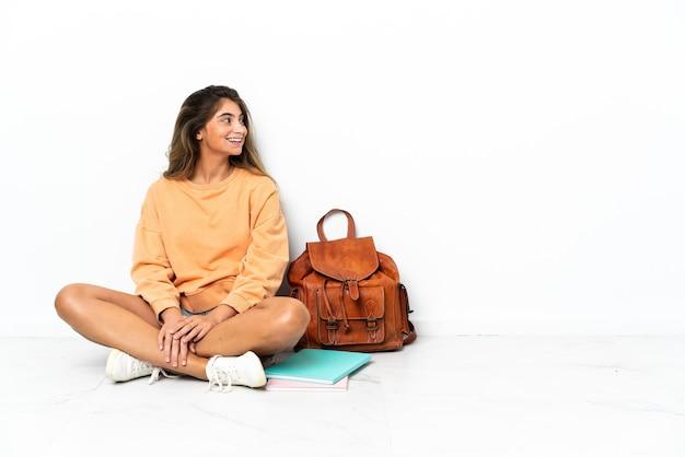 Giovane donna dell'allievo che si siede sul pavimento con un computer portatile isolato sulla parete bianca che osserva lato