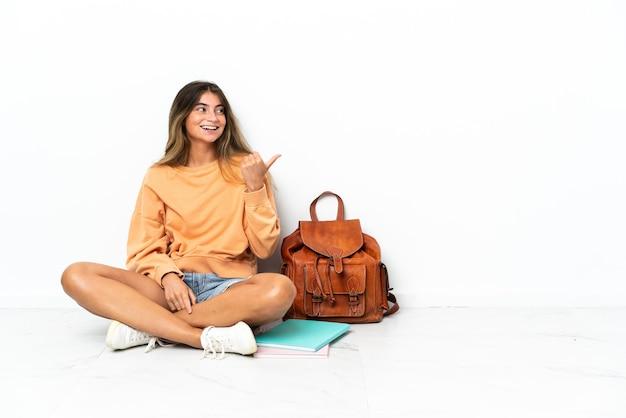 Donna giovane studente seduta sul pavimento con un computer portatile isolato sul muro bianco che punta di lato per presentare un prodotto