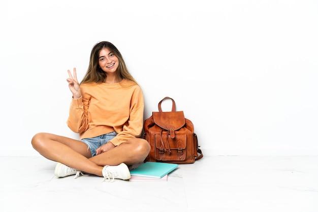 Giovane donna dell'allievo che si siede sul pavimento con un computer portatile isolato sulla parete bianca che sorride e che mostra il segno di vittoria