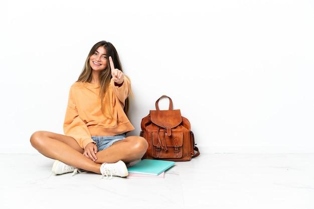 Donna giovane studente seduto sul pavimento con un computer portatile isolato