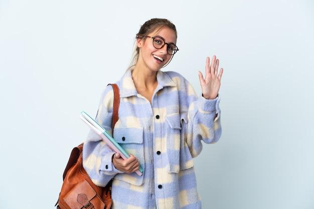 Giovane donna dell'allievo su bianco che saluta con la mano con l'espressione felice