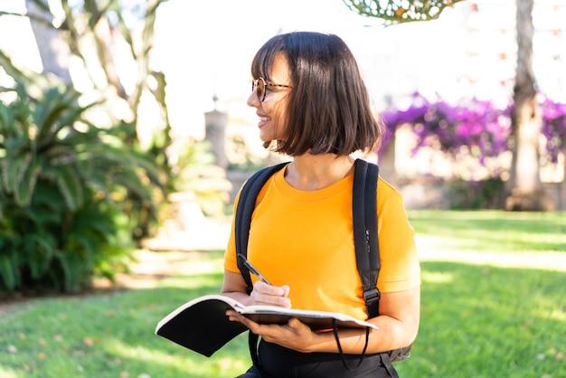 La giovane studentessa vince un parco con in mano un taccuino