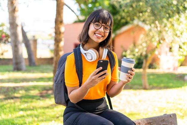 Giovane studentessa vince un parco usando il cellulare e tenendo in mano un caffè da asporto