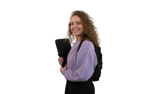 La giovane donna dell'allievo con uno zaino sta tenendo un computer