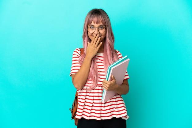 Giovane studentessa con i capelli rosa isolata su sfondo blu felice e sorridente che copre la bocca con la mano