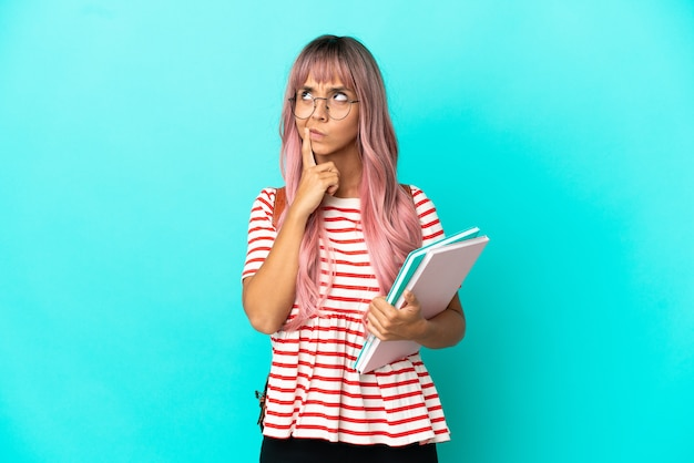 Giovane studentessa con i capelli rosa isolata su sfondo blu che ha dubbi mentre guarda in alto