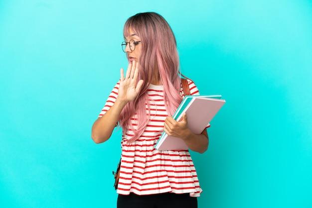 Giovane studentessa con i capelli rosa isolata su sfondo blu che fa un gesto di arresto e delusa