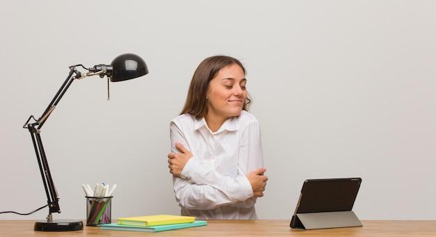 Giovane donna dello studente che lavora al suo scrittorio che dà un abbraccio
