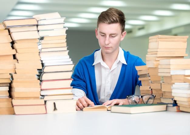 Giovani studenti che studiano e ricercano nella biblioteca del college con una pila di libri